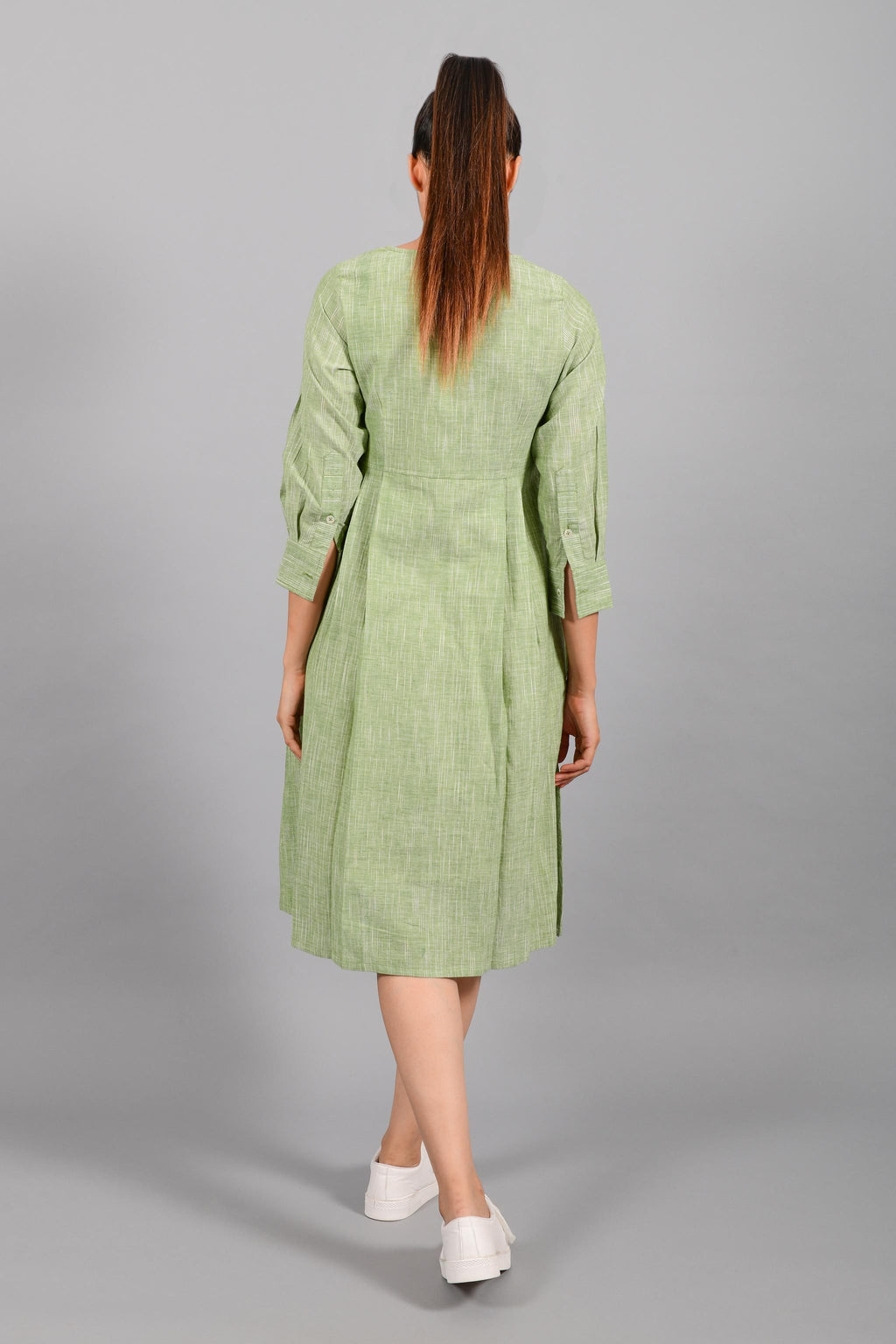 Back pose of an Indian female womenswear fashion model in a space dyed olive green handspun and handwoven khadi cotton pleated dress-kurta by Cotton Rack.