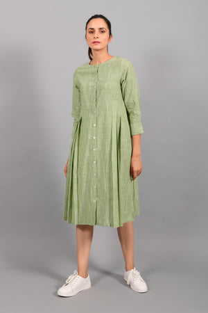 Front pose of an Indian female womenswear fashion model in a space dyed olive green handspun and handwoven khadi cotton pleated dress-kurta by Cotton Rack.