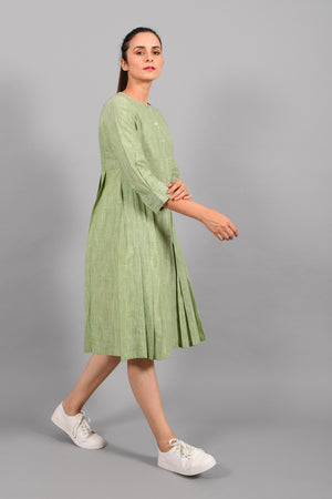 Stylised side pose of an Indian female womenswear fashion model in a space dyed olive green handspun and handwoven khadi cotton pleated dress-kurta by Cotton Rack.