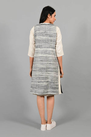 Back pose of an Indian Womenswear female model wearing black and white thicker handspun and handwoven khadi Jacket over a Cashemer Cotton Dress by Cotton Rack.