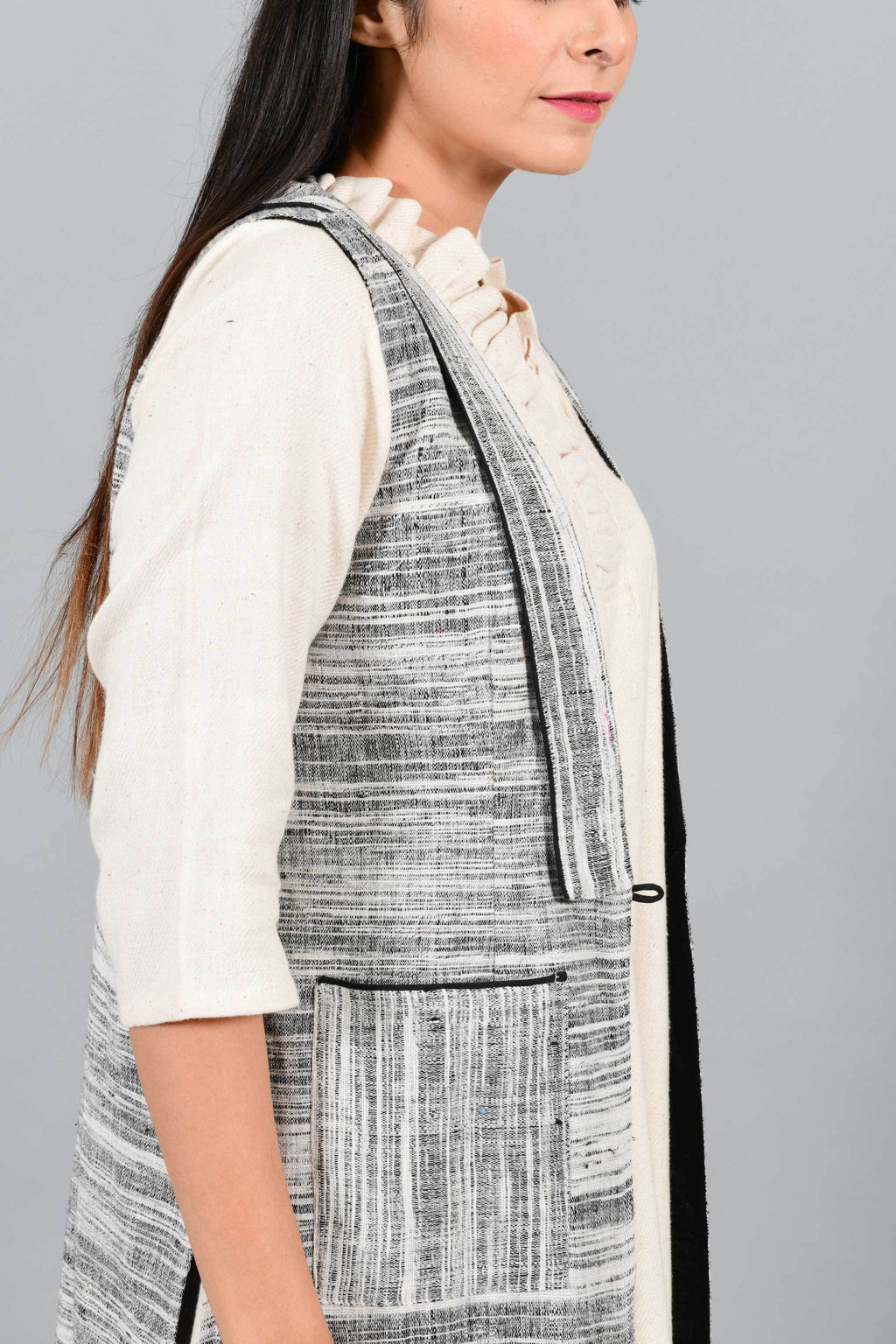 Side close up of an Indian Womenswear female model wearing black and white thicker handspun and handwoven khadi Jacket over a Cashemer Cotton Dress by Cotton Rack.