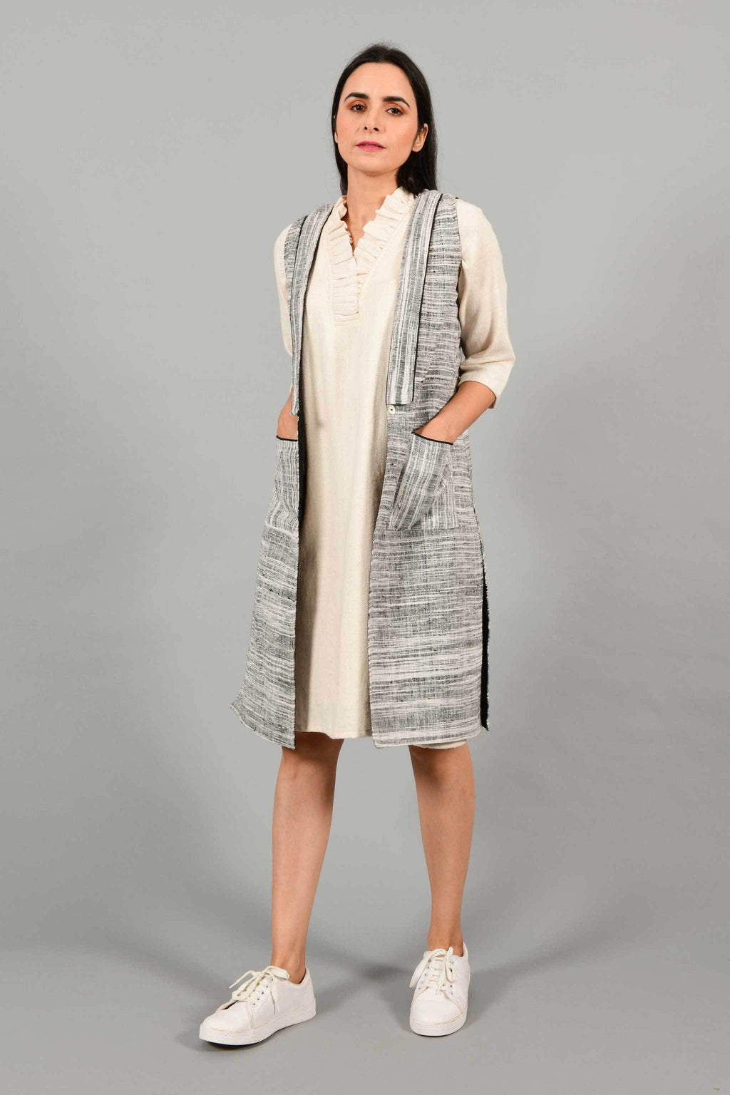 Front pose of an Indian Womenswear female model wearing black and white thicker handspun and handwoven khadi Jacket over a Cashemer Cotton Dress by Cotton Rack.