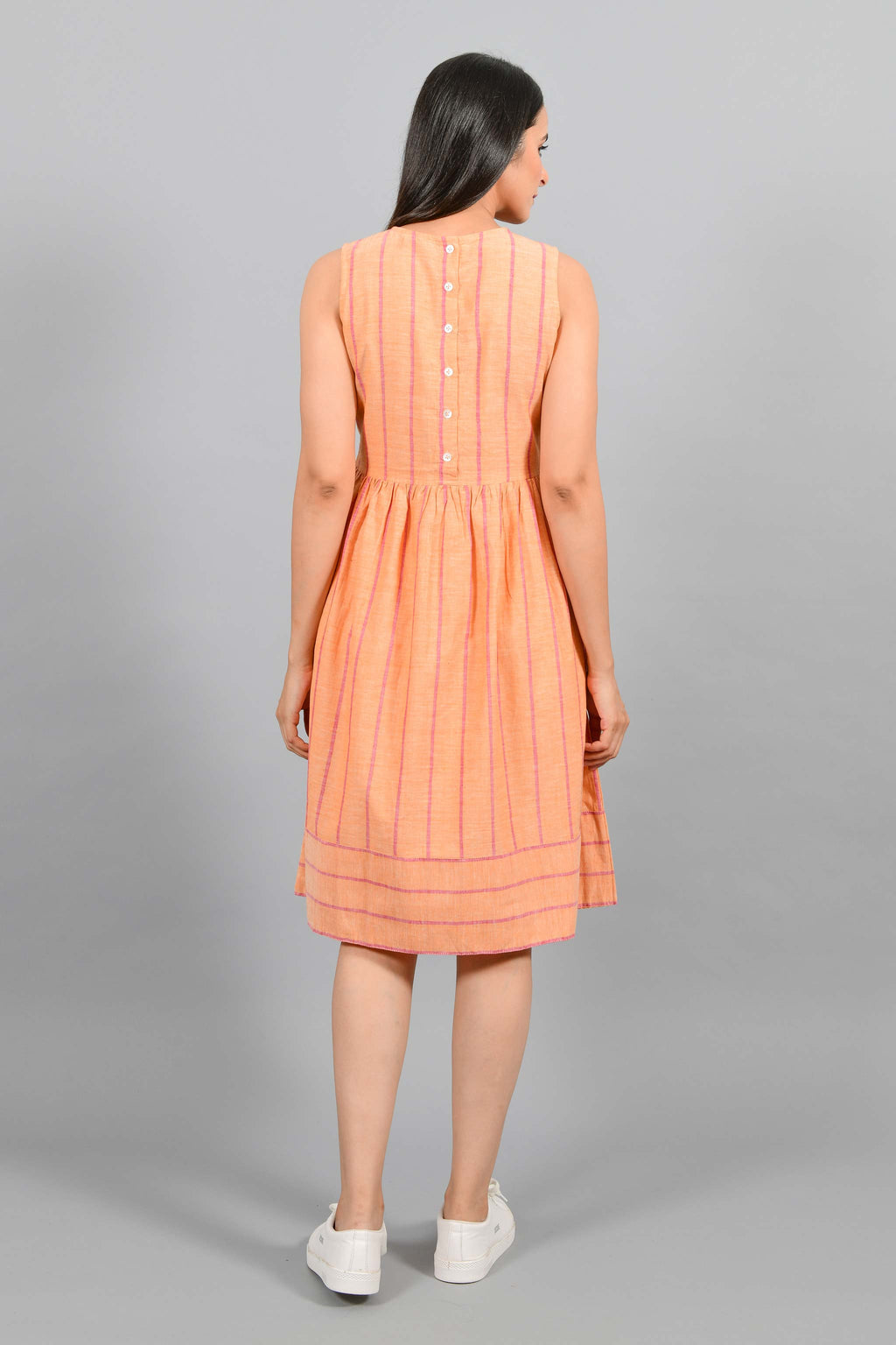 Back pose of an Indian female womenswear fashion model in a orange chambray handspun and handwoven khadi cotton with red stripes by Cotton Rack. The dress has gathers at waist. and the stripes are arranged in attractive manner.