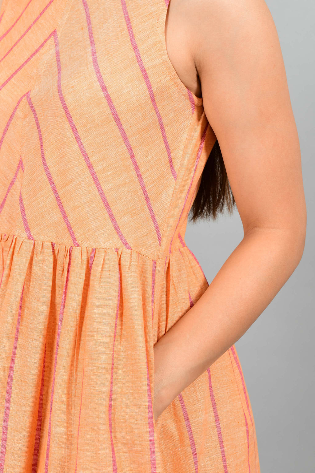 Close up of an Indian female womenswear fashion model in a orange chambray handspun and handwoven khadi cotton with red stripes by Cotton Rack. The dress has gathers at waist. and the stripes are arranged in attractive manner.