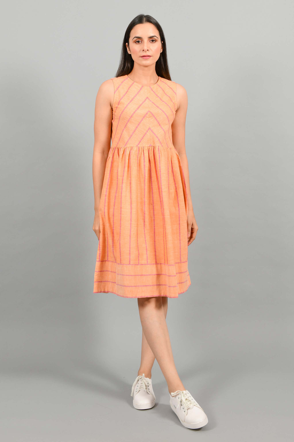 Front pose of an Indian female womenswear fashion model in a orange chambray handspun and handwoven khadi cotton with red stripes by Cotton Rack. The dress has gathers at waist. and the stripes are arranged in attractive manner.