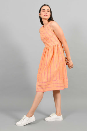 Stylised Side pose of an Indian female womenswear fashion model in a orange chambray handspun and handwoven khadi cotton with red stripes by Cotton Rack. The dress has gathers at waist. and the stripes are arranged in attractive manner.