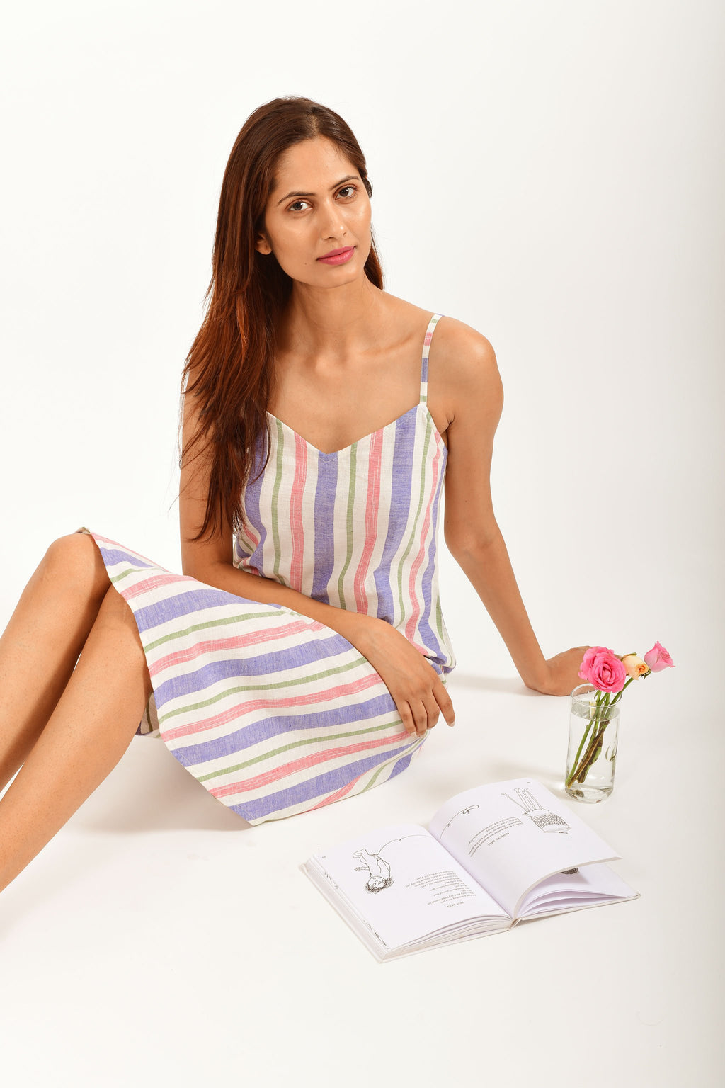 Stylized pose of an Indian female womenswear fashion model in an mutli colored striped handspun and handwoven khadi cotton spaghetti dress by Cotton Rack sitting on the floor and reading A Light In The Attic by Shel Silverstein.