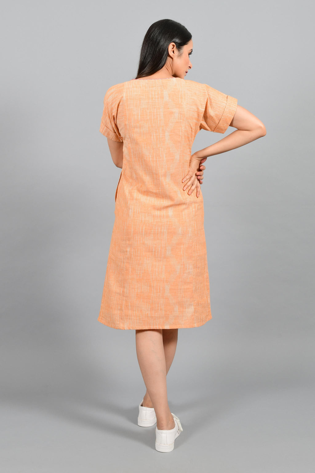 Back pose of an Indian female womenswear fashion model in an orange space dyed handspun and handwoven khadi cotton panelled dress by Cotton Rack.