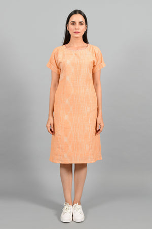 Front pose of an Indian female womenswear fashion model in an orange space dyed handspun and handwoven khadi cotton panelled dress by Cotton Rack.