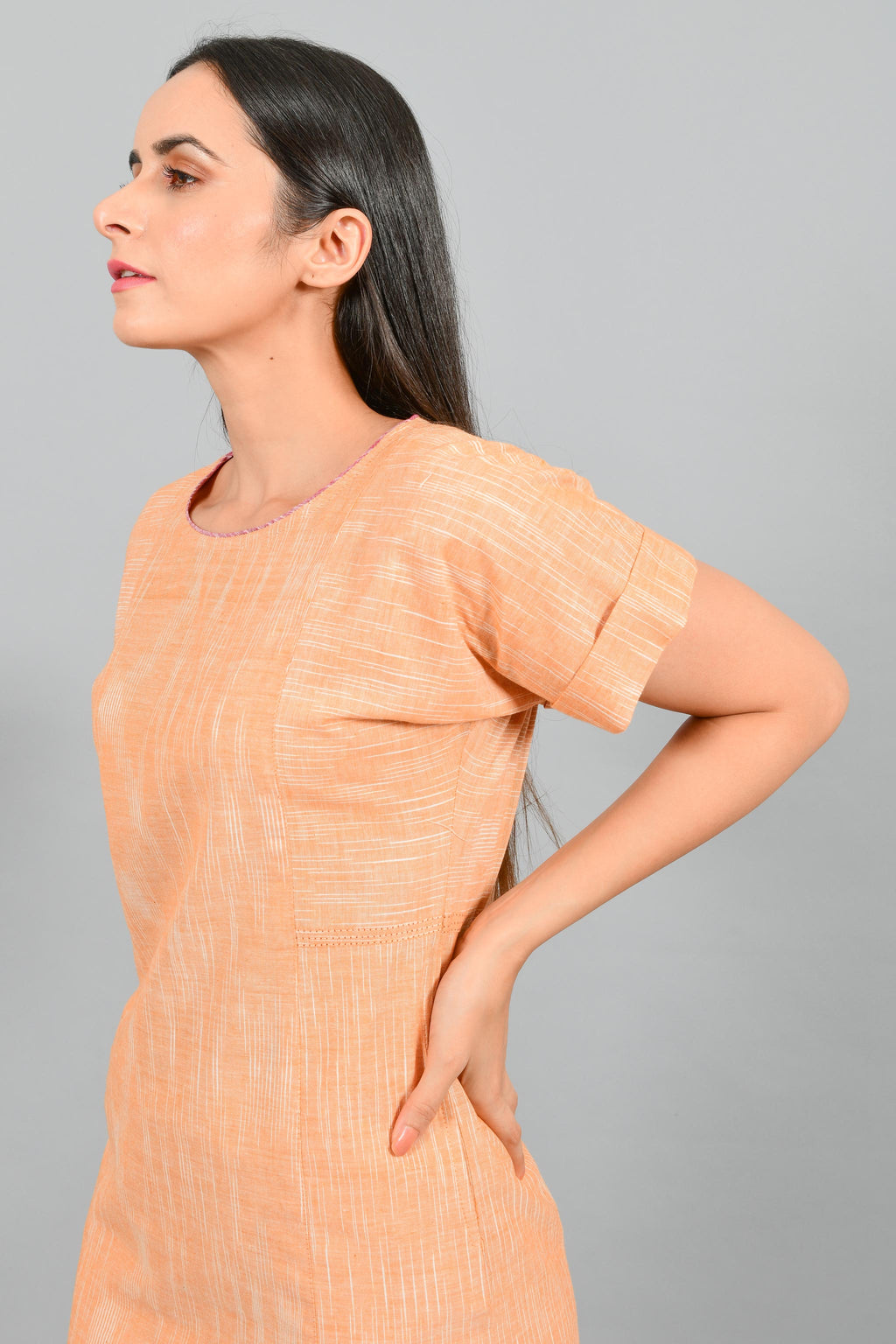Side close up portrait of an Indian female womenswear fashion model in an orange space dyed handspun and handwoven khadi cotton panelled dress by Cotton Rack.