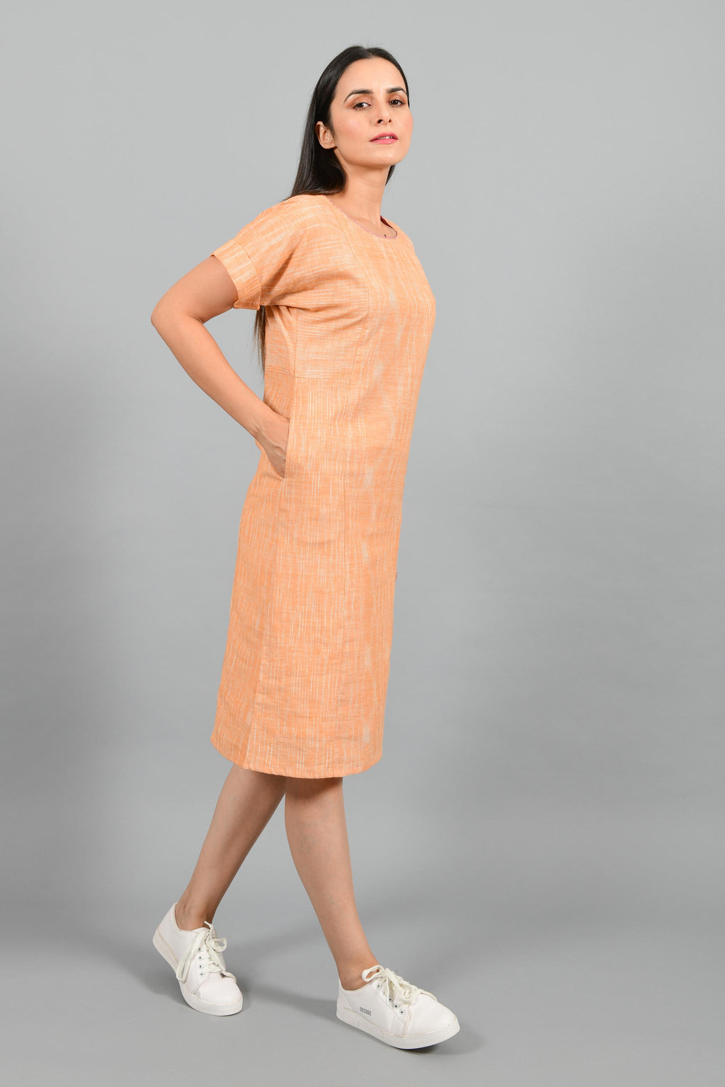 Stylised side pose of an Indian female womenswear fashion model in an orange space dyed handspun and handwoven khadi cotton panelled dress by Cotton Rack.
