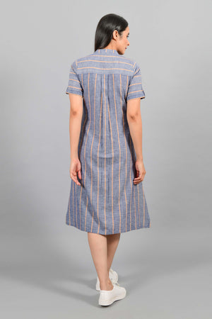 Back pose of an Indian female womenswear fashion model in a Blue chambray with orange stripes handspun and handwoven khadi cotton dress-kurta by Cotton Rack.