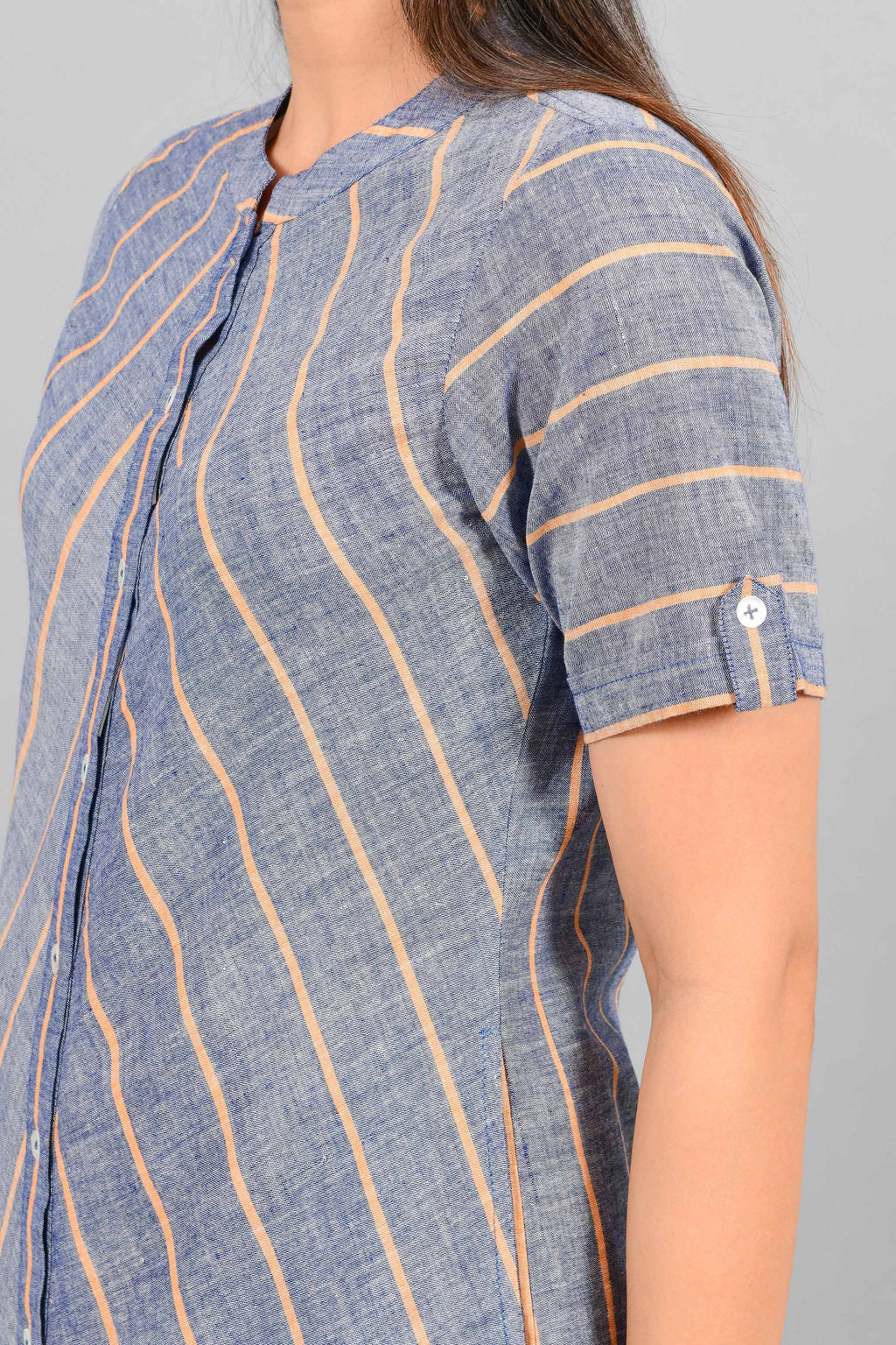 Close Up of an Indian female womenswear fashion model in a Blue chambray with orange stripes handspun and handwoven khadi cotton dress-kurta by Cotton Rack.