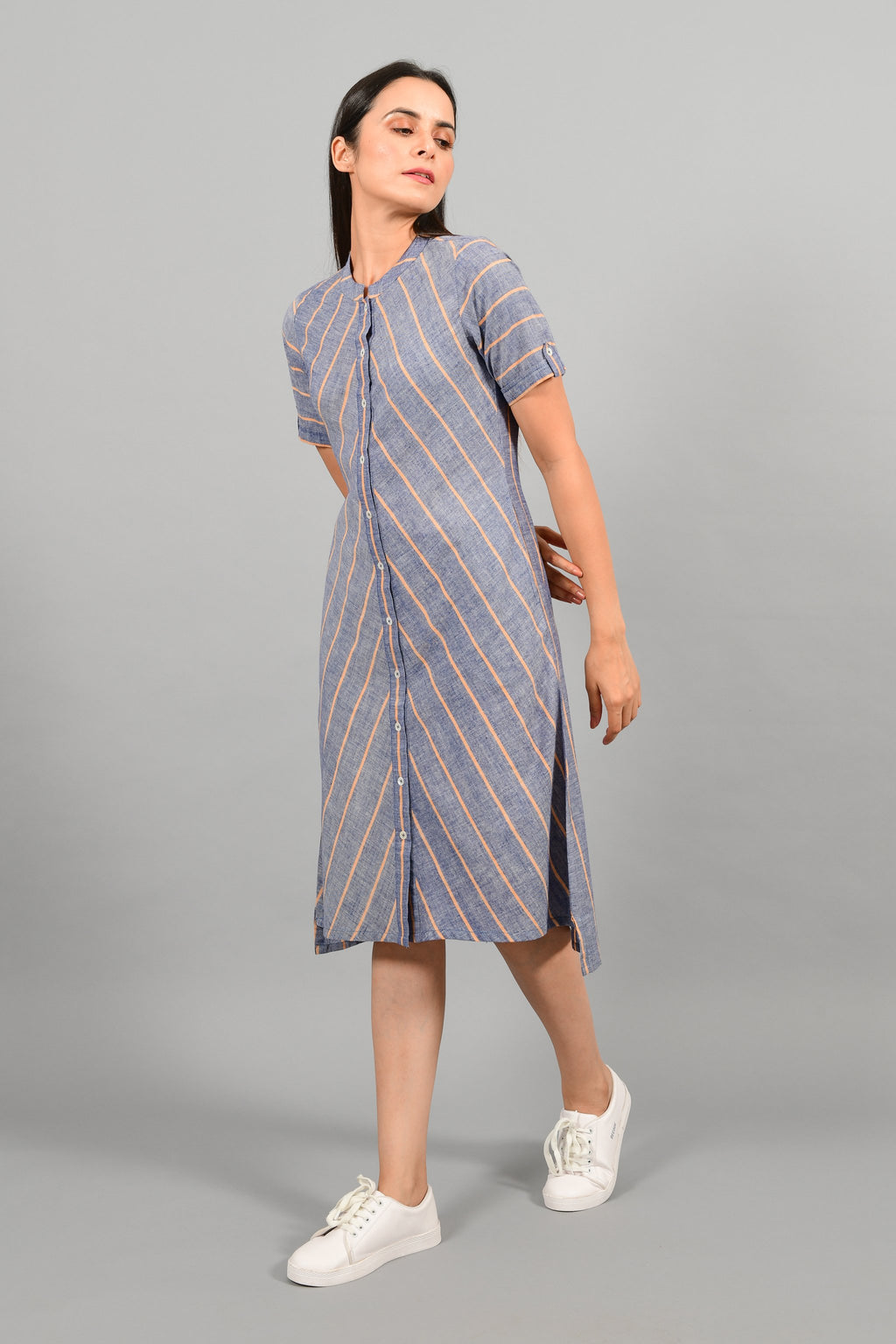 Side pose of an Indian female womenswear fashion model in a Blue chambray with orange stripes handspun and handwoven khadi cotton dress-kurta by Cotton Rack.