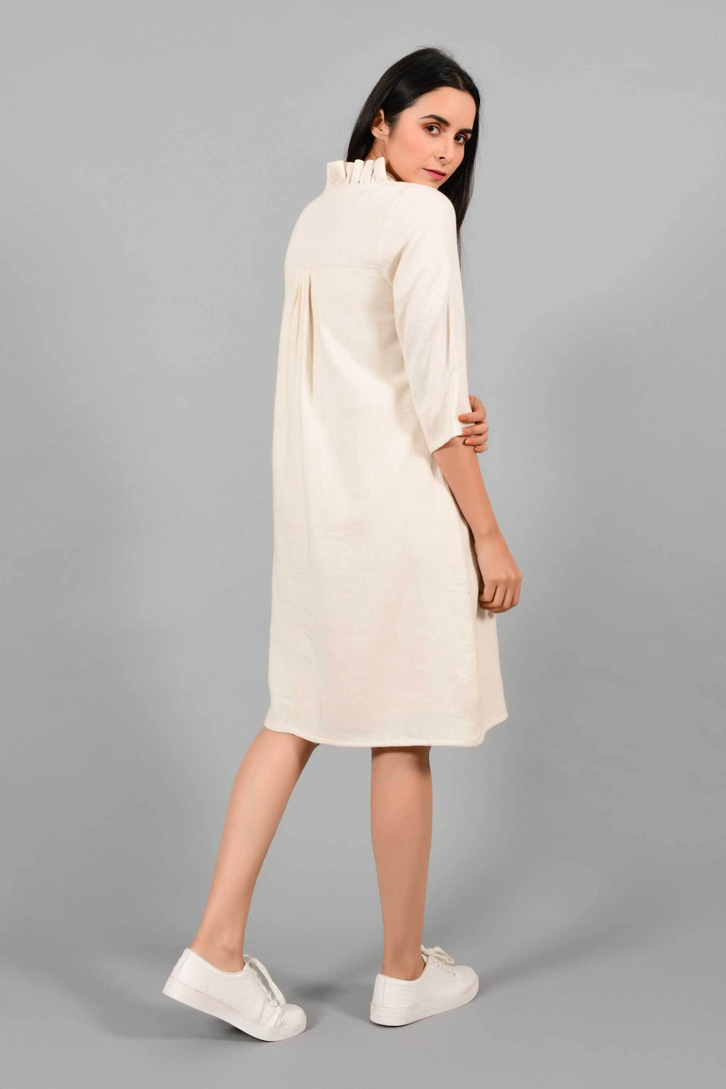 Back pose of an Indian female womenswear fashion model in an off-white Cashmere Cotton Dress with flared neck, made using handspun and handwoven khadi cotton by Cotton Rack.