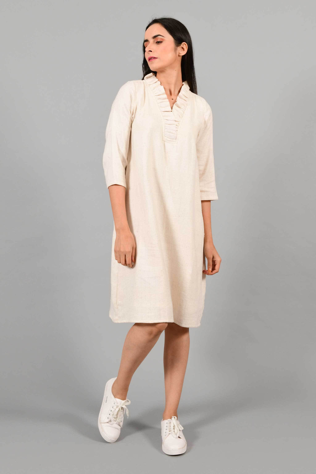Stylised front pose of an Indian female womenswear fashion model in an off-white Cashmere Cotton Dress with flared neck, made using handspun and handwoven khadi cotton by Cotton Rack.