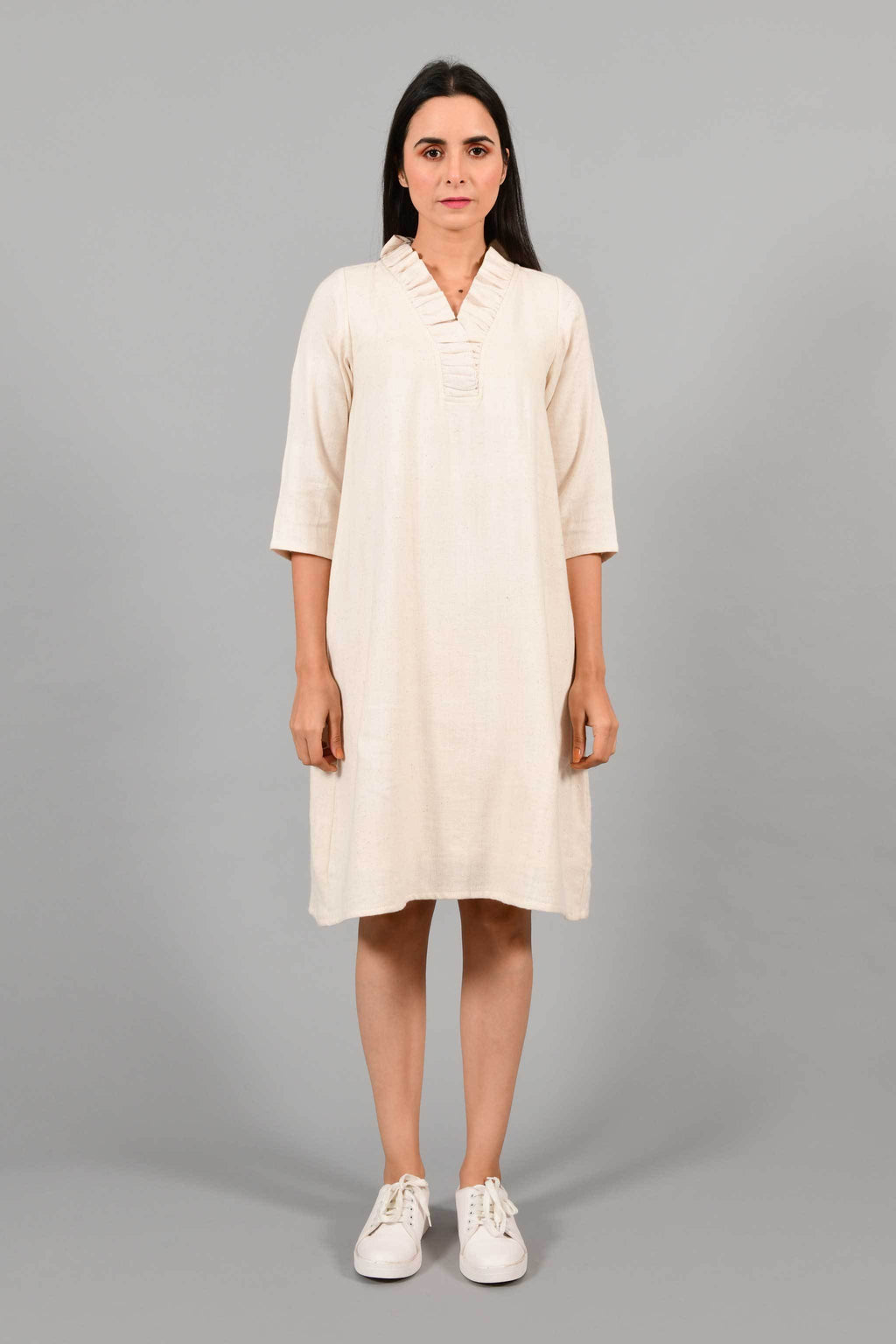Front pose of an Indian female womenswear fashion model in an off-white Cashmere Cotton Dress with flared neck, made using handspun and handwoven khadi cotton by Cotton Rack.