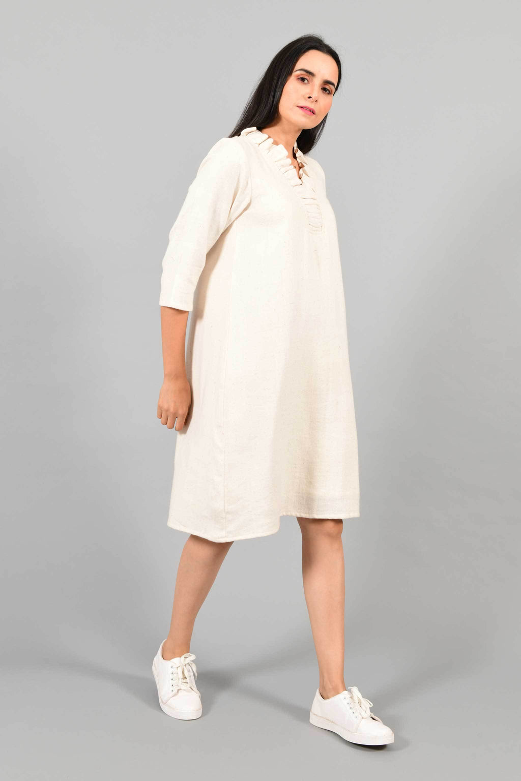 Side pose of an Indian female womenswear fashion model in an off-white Cashmere Cotton Dress with flared neck, made using handspun and handwoven khadi cotton by Cotton Rack.