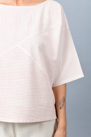 Closeup of model in an anti-fit crop top with metal block printed with red stripes in fine off-white khadi cotton paired with white shoes and khadi palazzos.