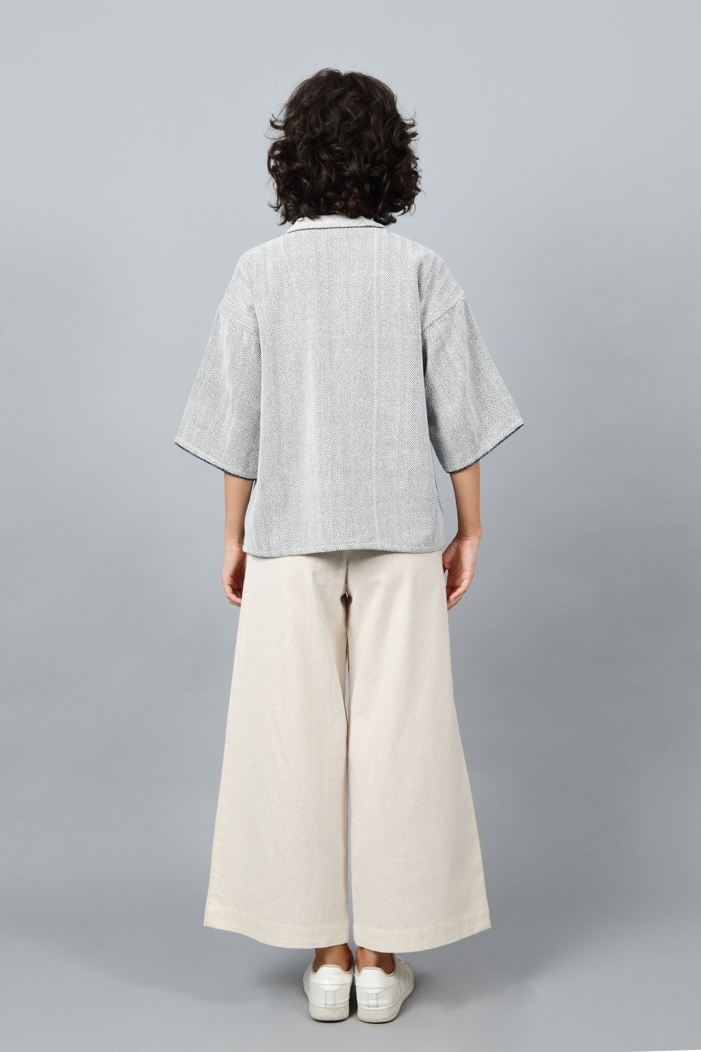 Back of a model wearing anti-fit short black shrug made in pointed twill with handspun and handwoven khadi cotton. Paired with off-white spaghetti, palazzos and white shoes.