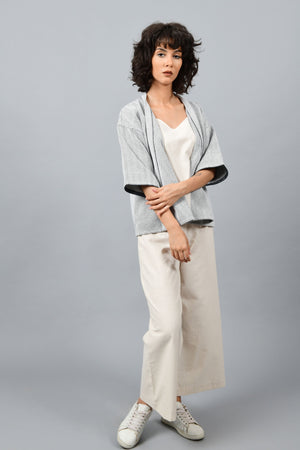 Model wearing anti-fit short black shrug made in pointed twill with handspun and handwoven khadi cotton. Paired with off-white spaghetti, palazzos and white shoes.