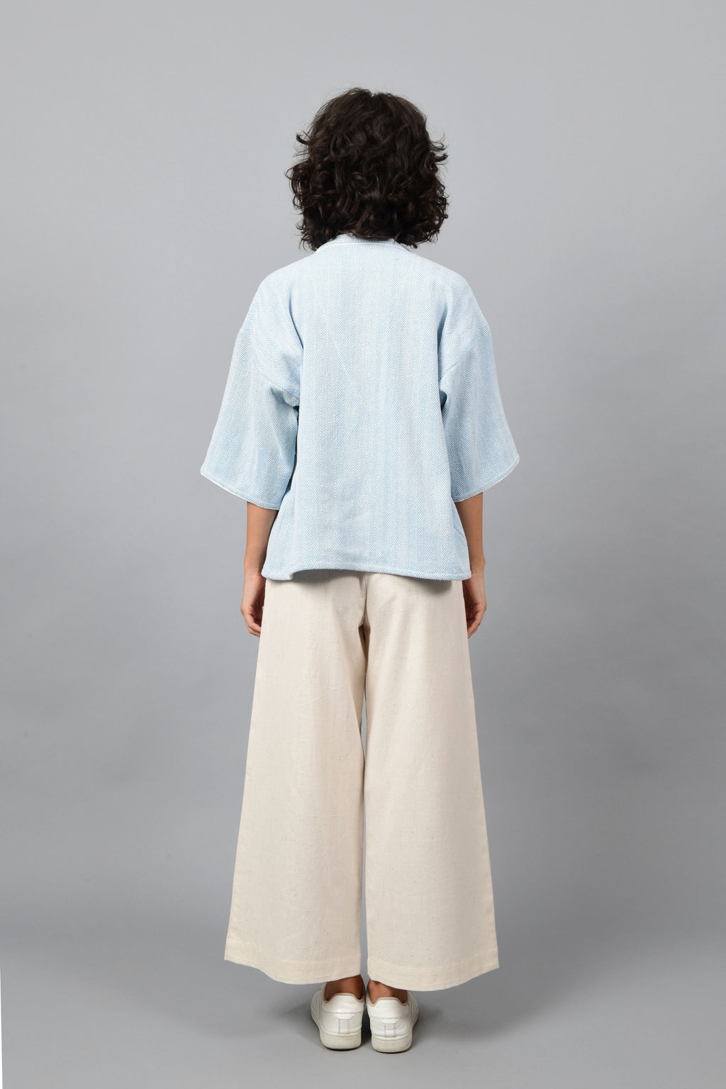 Back of a model wearing anti-fit short blue shrug made in pointed twill with handspun and handwoven khadi cotton. Paired with off-white spaghetti, palazzos and white shoes.
