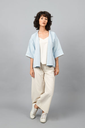 Model wearing anti-fit short blue shrug made in pointed twill with handspun and handwoven khadi cotton. Paired with off-white spaghetti, palazzos and white shoes.