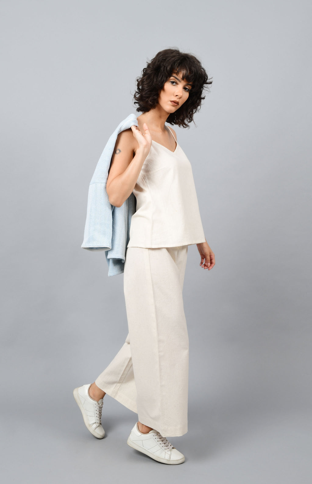 A model holding an anti-fit short grey shrug made in pointed twill with handspun and handwoven khadi cotton in her hands on the back while walking.