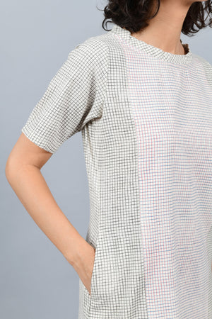 close-up of a model wearing a boat neck panel dress printed with black checks and red and blue checks in the panel using brass block printing over handspun handwoven khadi cotton from maheshwar