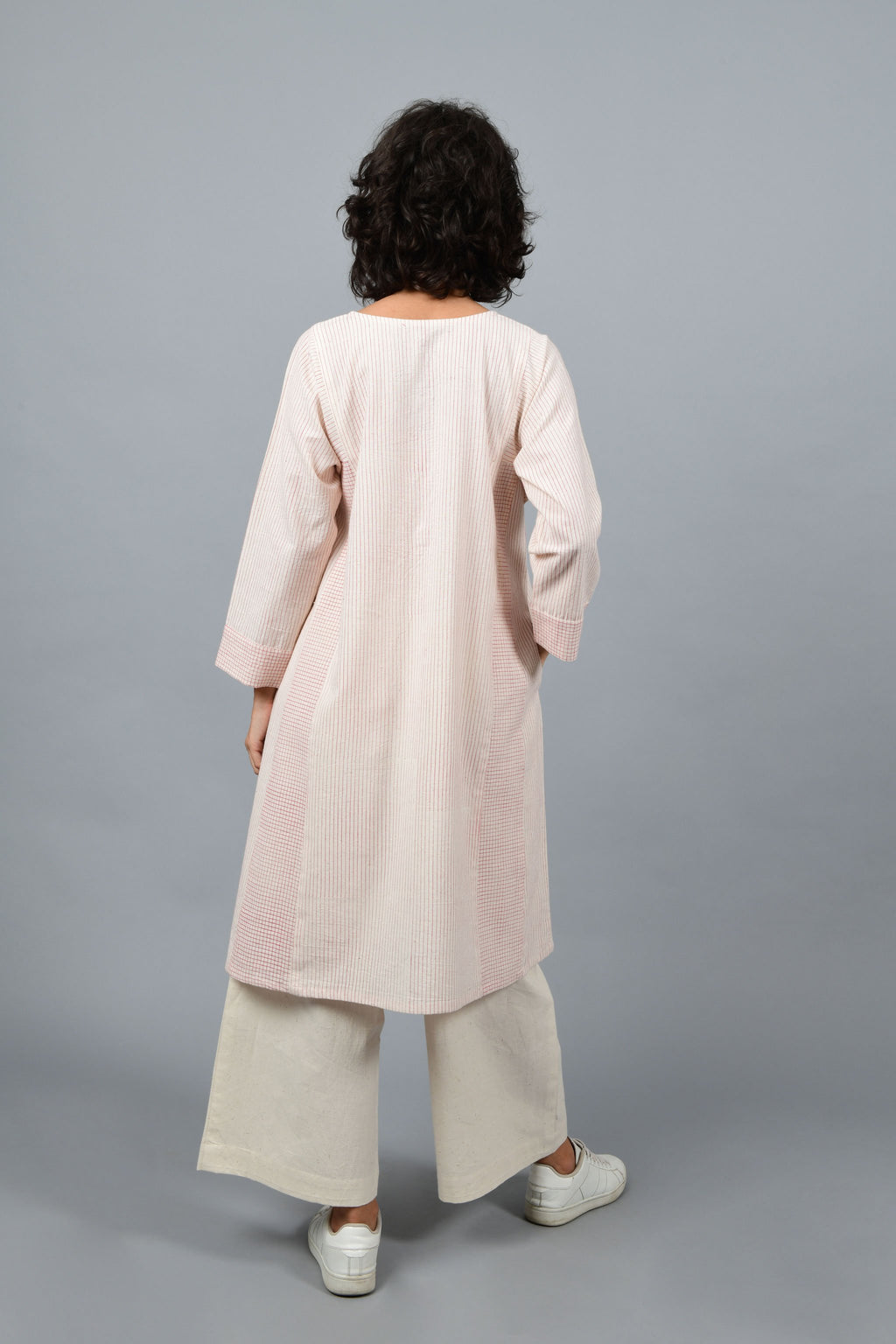 back of a womenswear fashion model wearing a minimally designed modern kalidar dress kurta printed by Cotton Rack with fine red checks using brass block printing over handspun handwoven khadi cotton from maheshwar