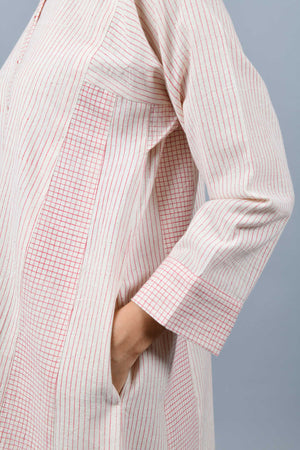 close-up of the side-seam of a model wearing a modern kalidar dress kurta printed with fine red checks using brass block printing over handspun handwoven khadi cotton from maheshwar