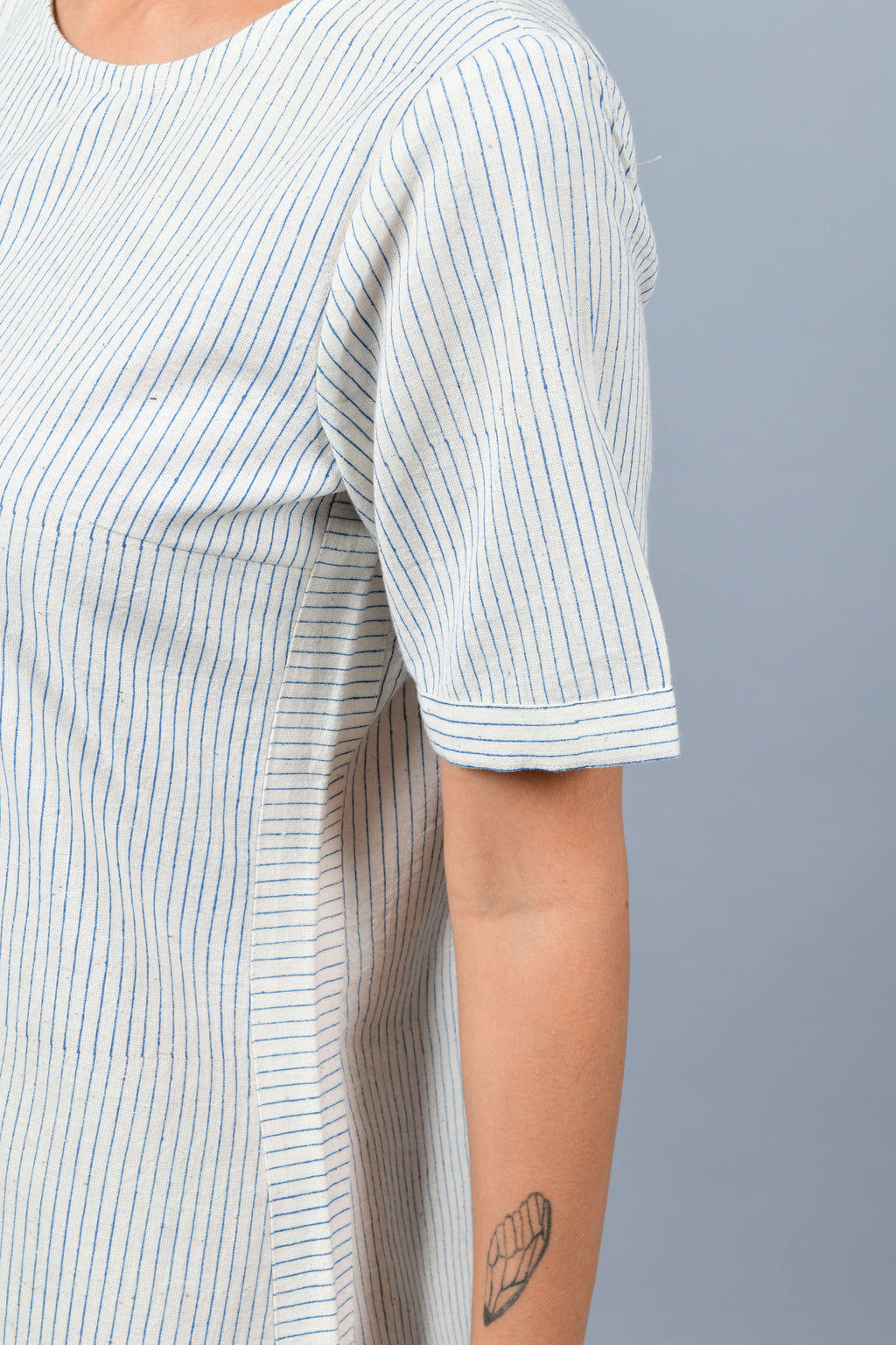 close-up of a womenswear fashion model wearing minimalistic a-line round bottom dress by Cotton Rack printed with blue stripes using brass block printing over handspun handwoven khadi cotton from maheshwar