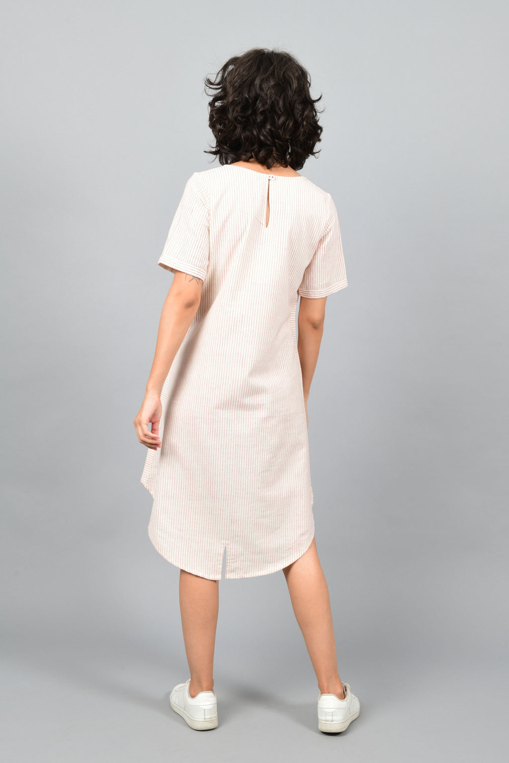back of a female womenswear fashion model wearing a minimal a-line round bottom dress Cotton Rack printed with red stripes with side-seam details using brass block printing over handspun handwoven khadi cotton from maheshwar