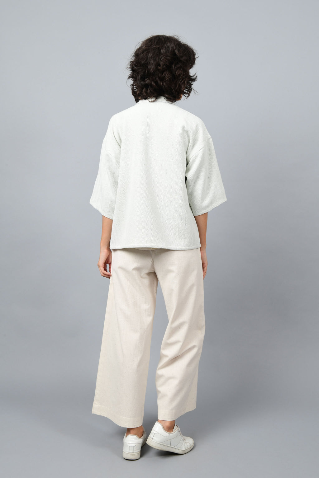 Back of a model wearing anti-fit short grey shrug made in pointed twill with handspun and handwoven khadi cotton. Paired with off-white spaghetti, palazzos and white shoes.