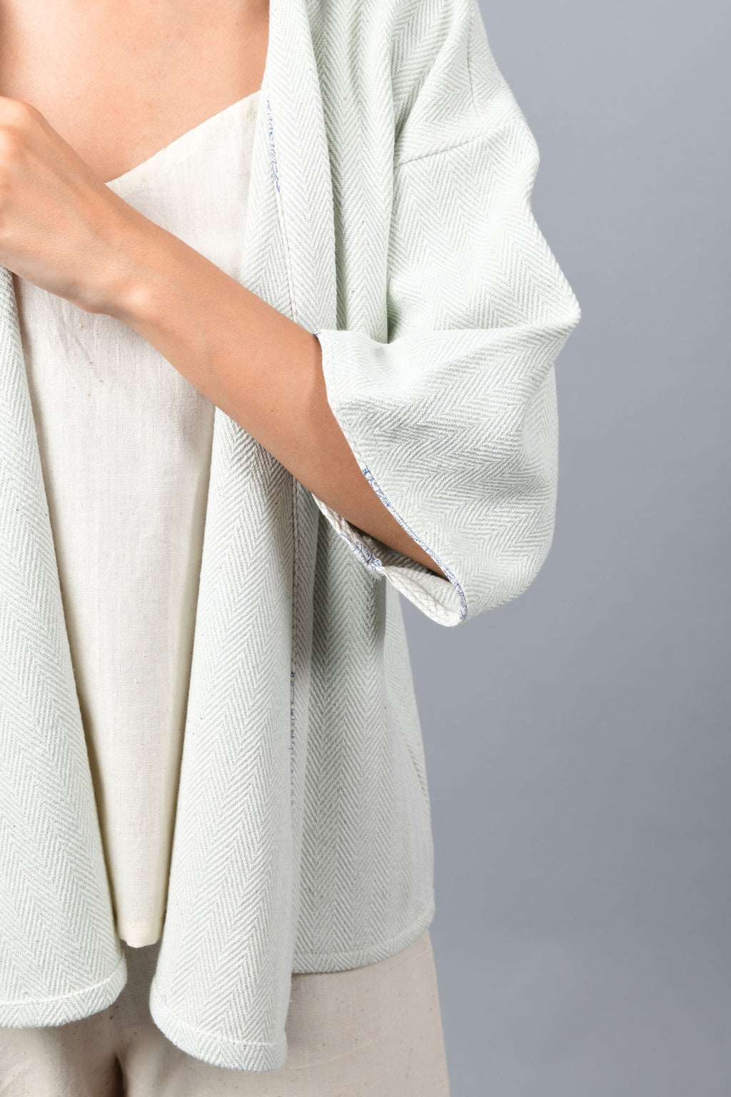 Close-Up of details of anti-fit short grey shrug made in pointed twill with handspun and handwoven khadi cotton. Paired with off-white spaghetti, palazzos.