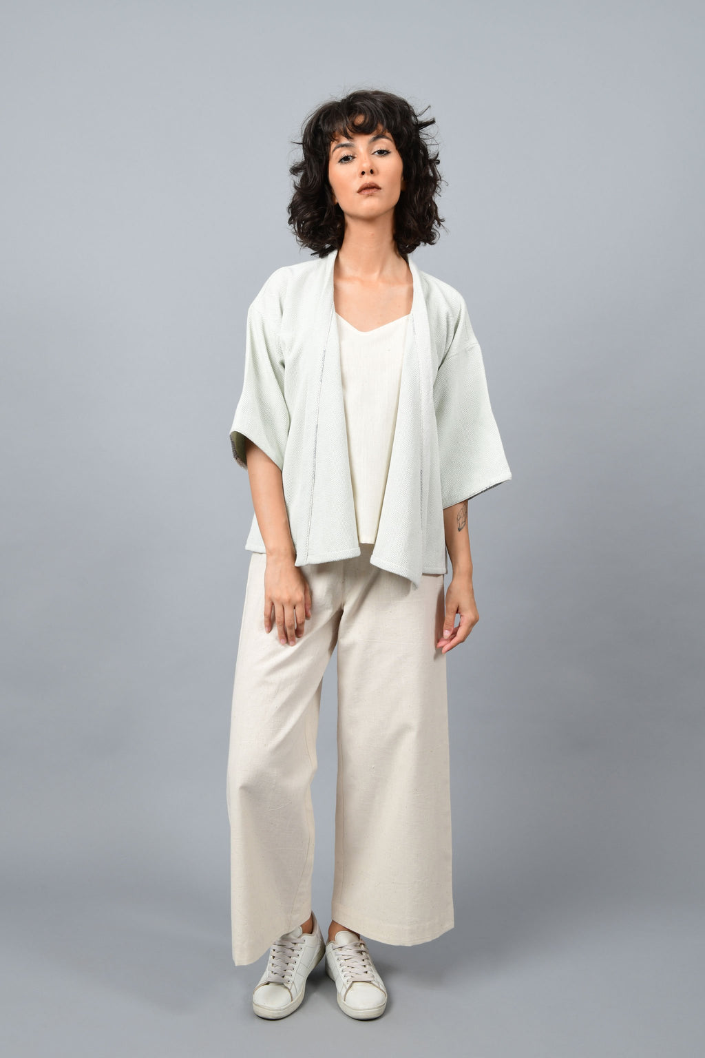 Model wearing anti-fit short grey shrug made in pointed twill with handspun and handwoven khadi cotton. Paired with off-white spaghetti, palazzos and white shoes.