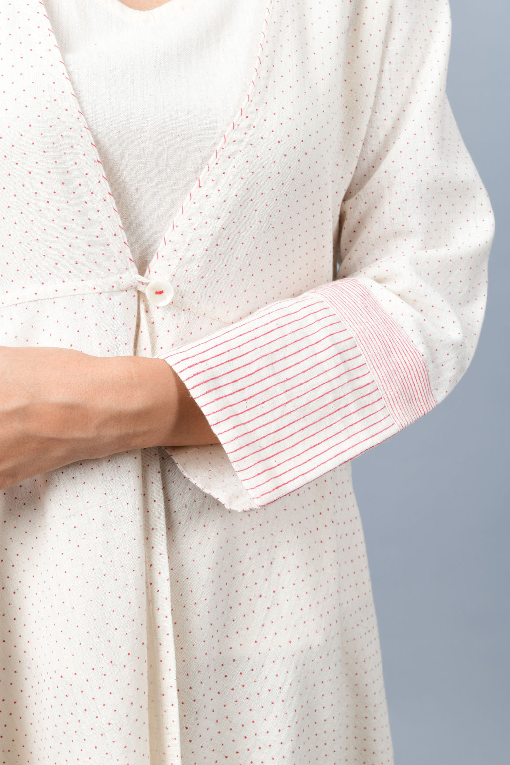 Close of a long flared off-white, natural khadi cotton shrug buttoned up in the front, hand block printed with fine red dots and red stripes on the sleeve hem.