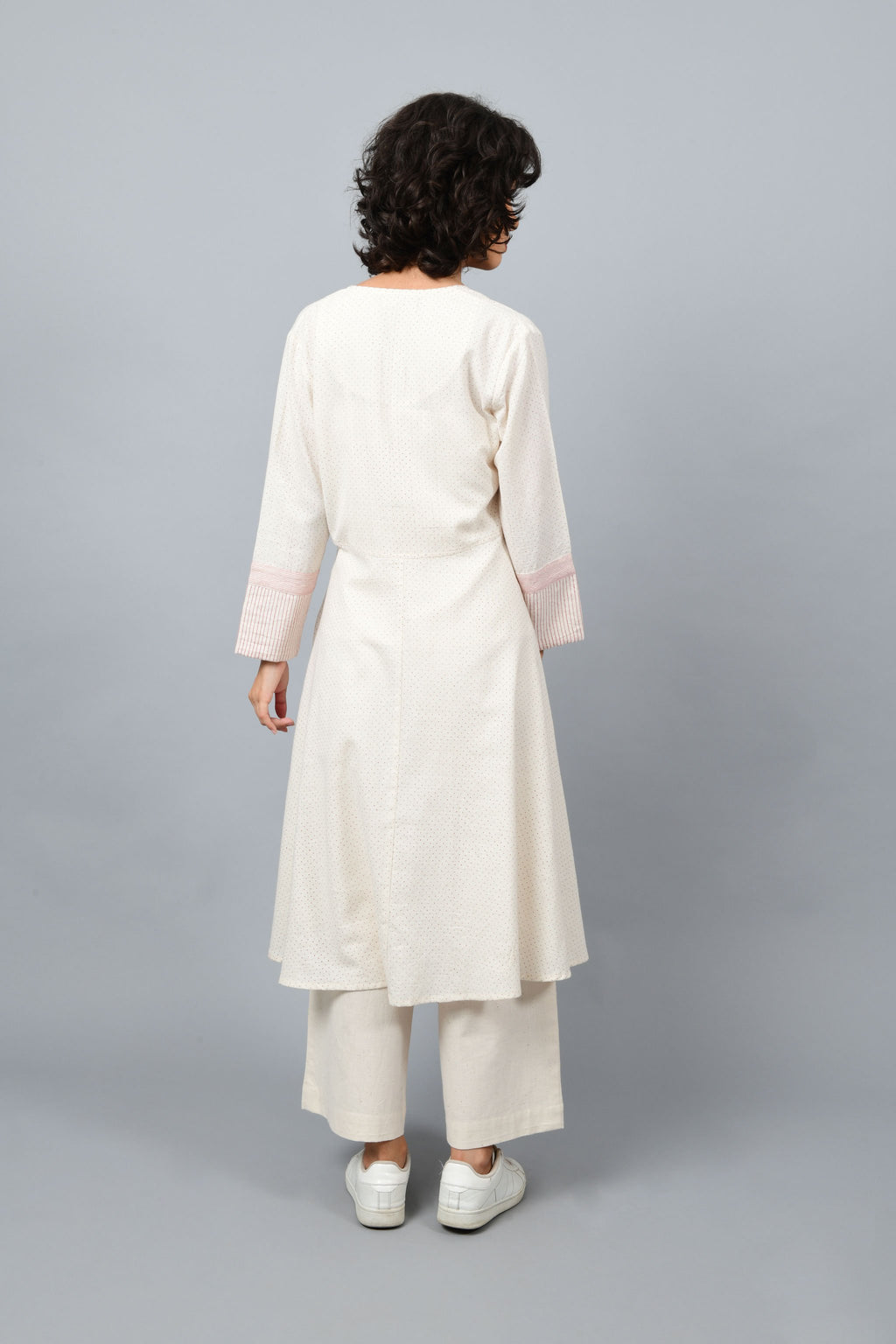 Back of the long flared off-white, natural khadi cotton shrug buttoned up, hand block printed with red dots and red stripes on the sleeve hem.