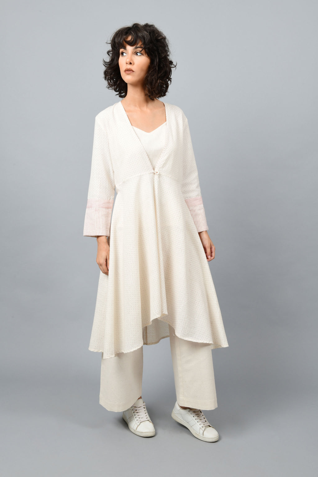 Model wearing a long flared off-white, natural khadi cotton shrug buttoned up in the front, hand block printed with red dots and red stripes on the sleeve hem.