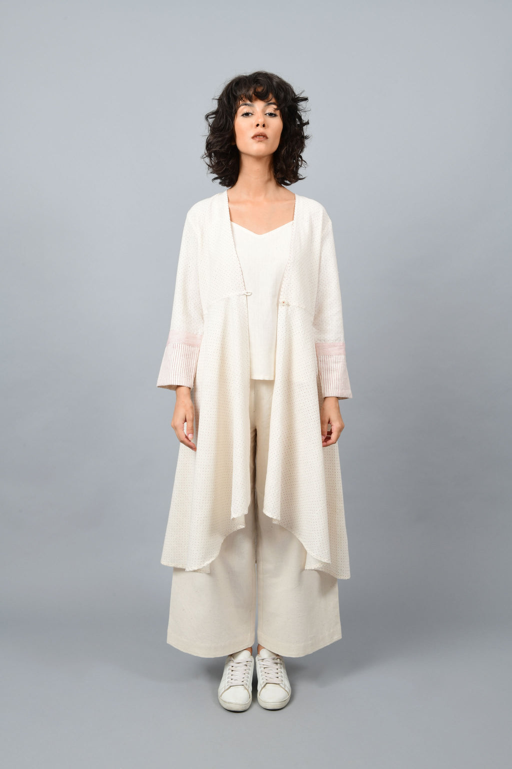Model wearing a long flared off-white, natural khadi cotton shrug, hand block printed with red dots and red stripes on the sleeve hem.