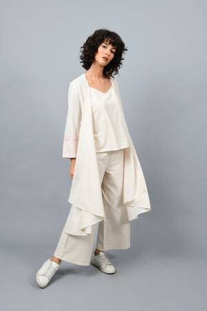 Model wearing a long flared off-white, natural khadi cotton shrug posing with quarter front and opened up in the front, hand block printed with red dots and red stripes on the sleeve hem.