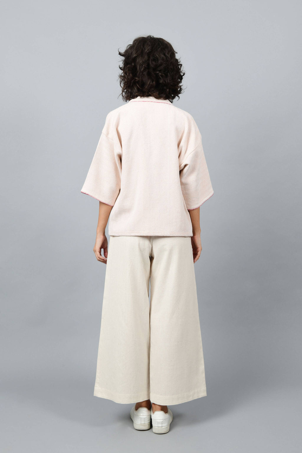 Back of a model wearing anti-fit short peach shrug made in pointed twill with handspun and handwoven khadi cotton. Paired with off-white spaghetti, palazzos and white shoes.