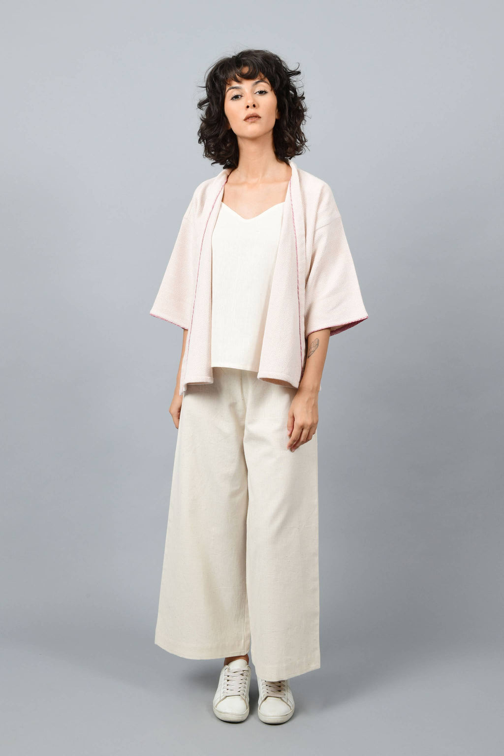 Model wearing anti-fit short peach shrug made in pointed twill with handspun and handwoven khadi cotton. Paired with off-white spaghetti, palazzos and white shoes.