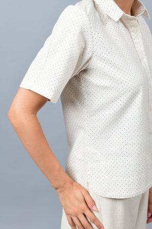Close up of the model wearing off-white Khadi cotton relaxed shirt top printed with fine blue dots printed using metal block by Cotton Rack inspired by artist agnes martin.
