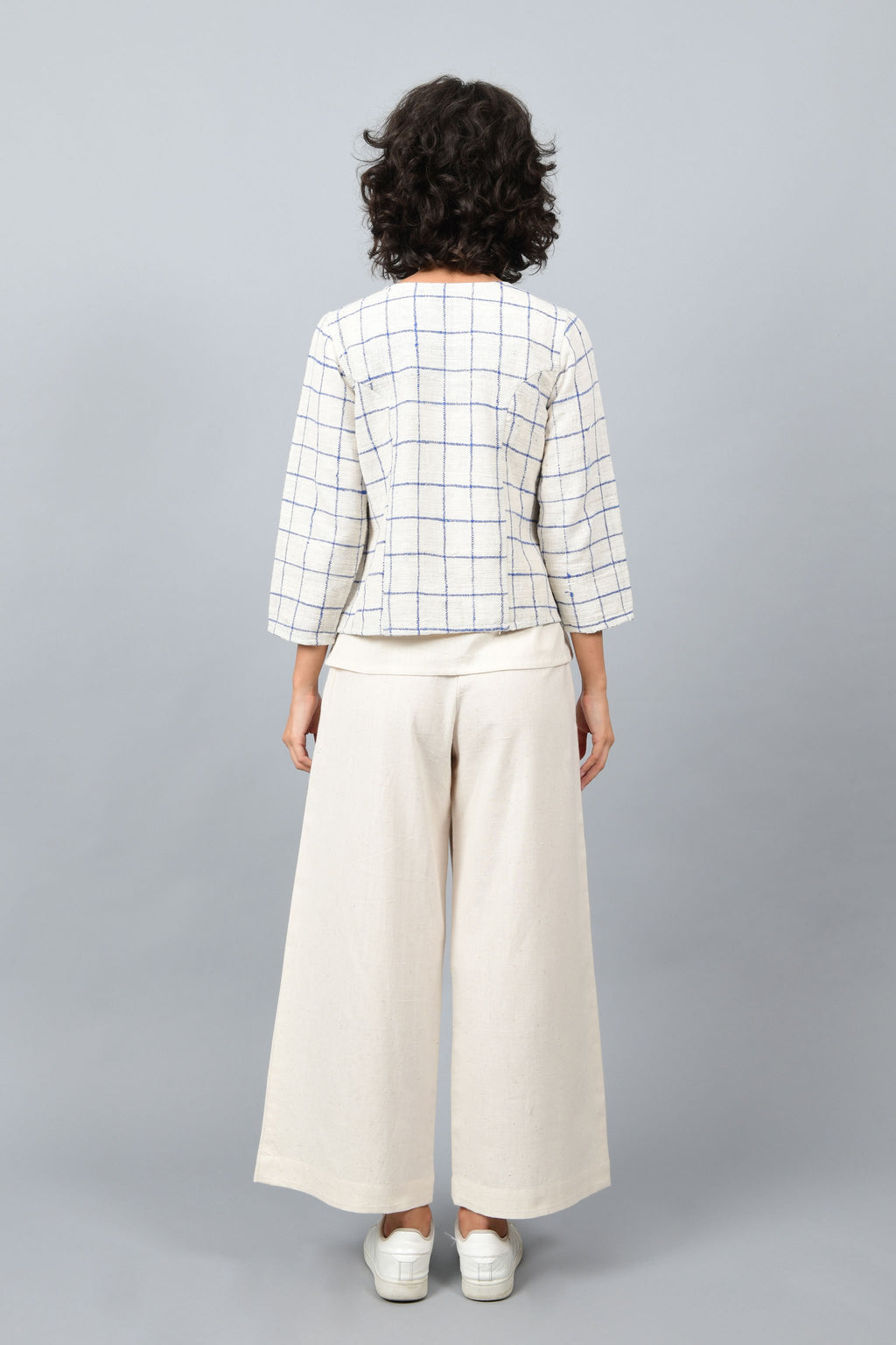 Model showing the back of open short jacket in thicker white handspun and handwoven khadi cotton with big blue checks over off-white spaghetti top and off-white palazzos paired with white sneakers.