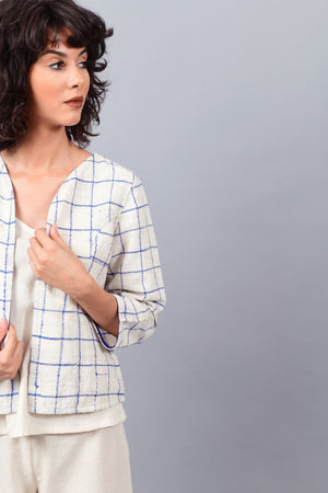 Close-up of model posing for the camera wearing open short jacket in thicker white handspun and handwoven khadi cotton with big blue checks over off-white spaghetti top and off-white palazzos paired with white sneakers.