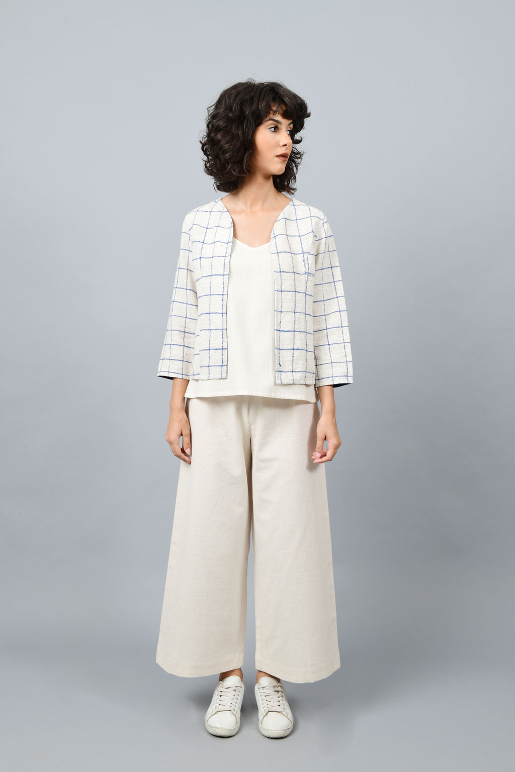 Model posing for the camera wearing open short jacket in thicker white handspun and handwoven khadi cotton with big blue checks over off-white spaghetti top and off-white palazzos paired with white sneakers.