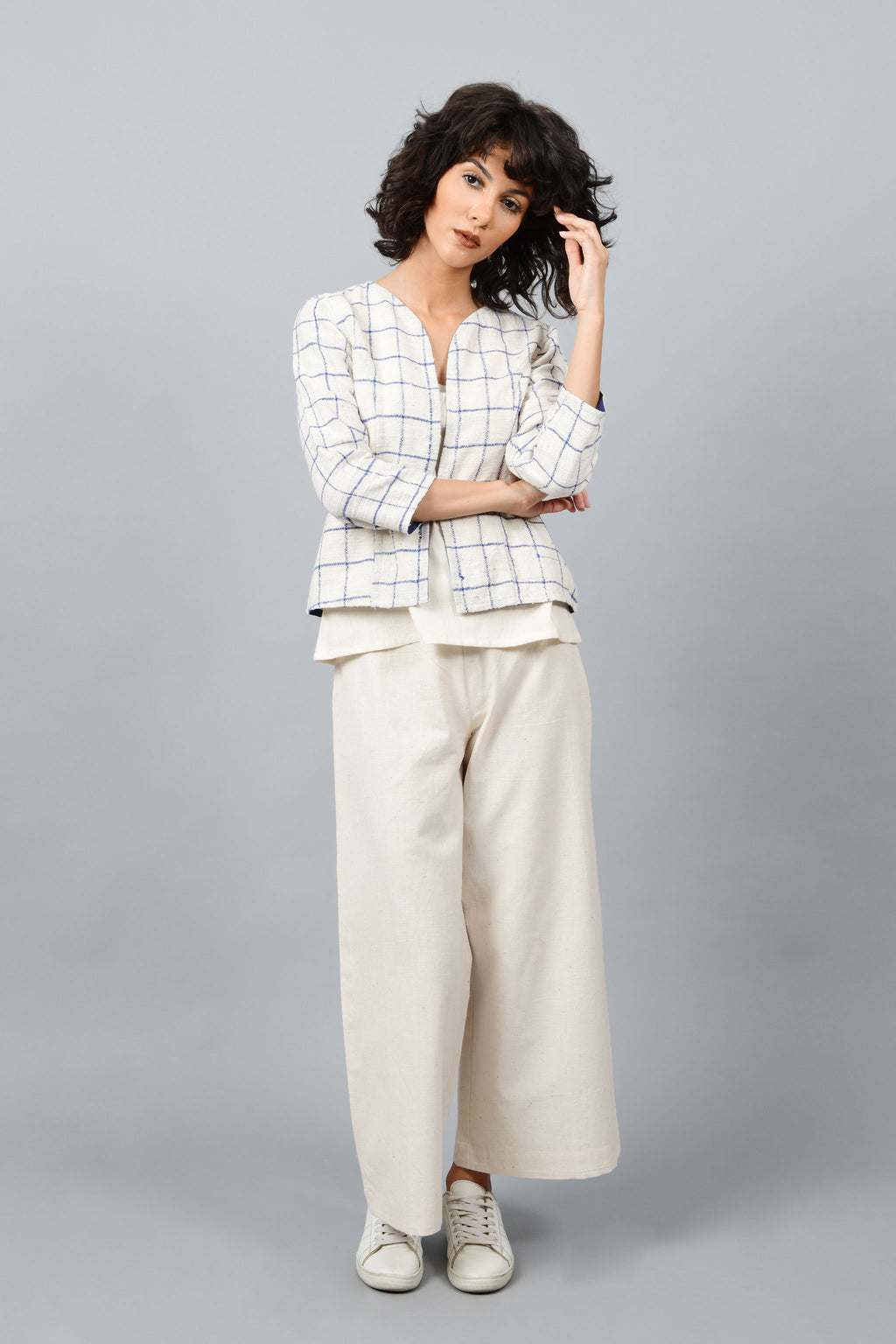 Brazilian Model posing for the camera wearing open short jacket in thicker white handspun and handwoven khadi cotton with big blue checks over off-white spaghetti top and off-white palazzos paired with white sneakers all made in India