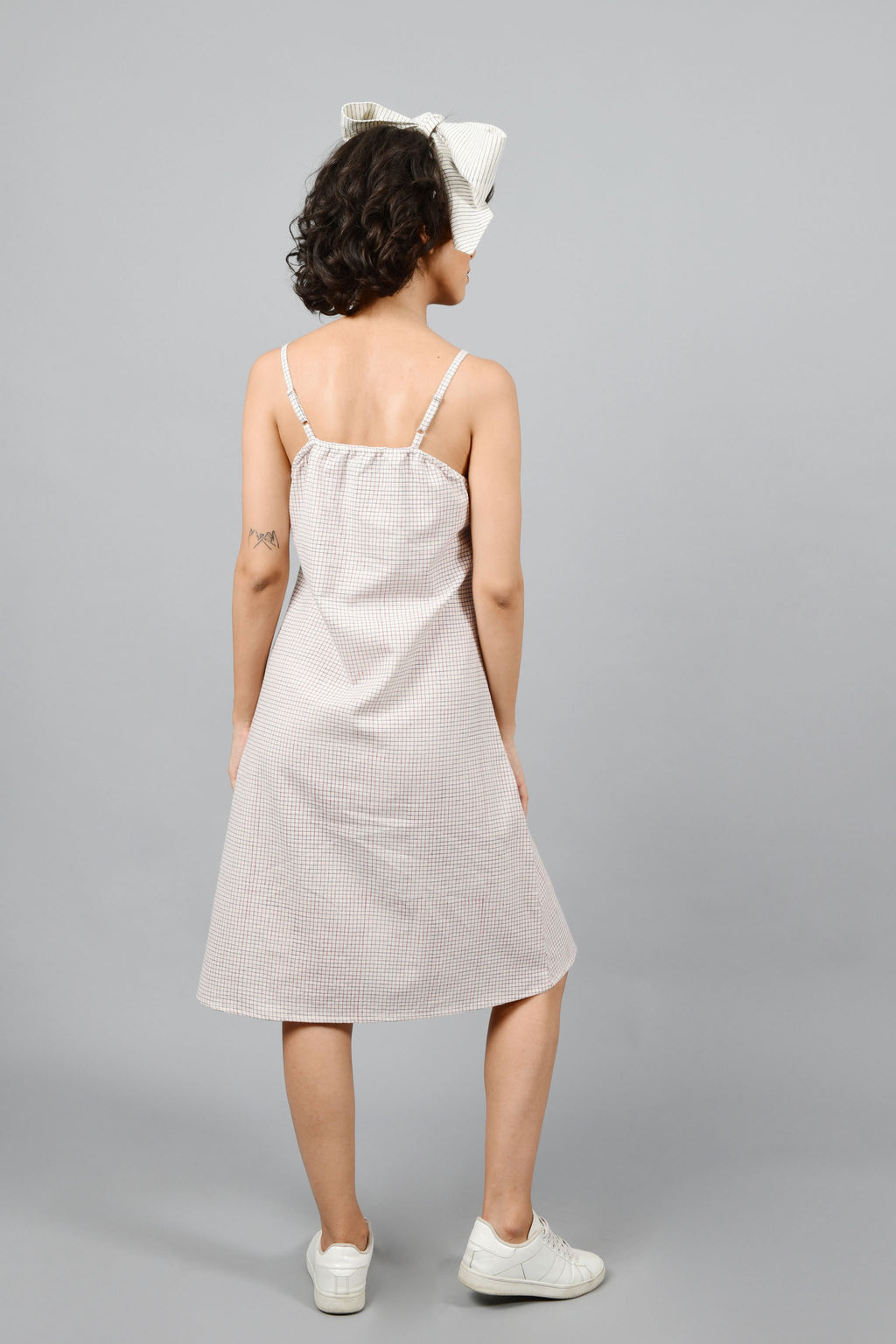 Model showing the back of the dress made by hand block printed handspun handwoven cotton khadi dress, printed with checks of red and blue on an off-white base. The model is also wearing an off-white printed bow in the same technique