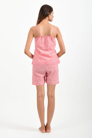Back pose of an Indian female womenswear fashion model in azo-free space dyed pink handspun and handwoven khadi cotton spaghetti top and boxers by Cotton Rack.